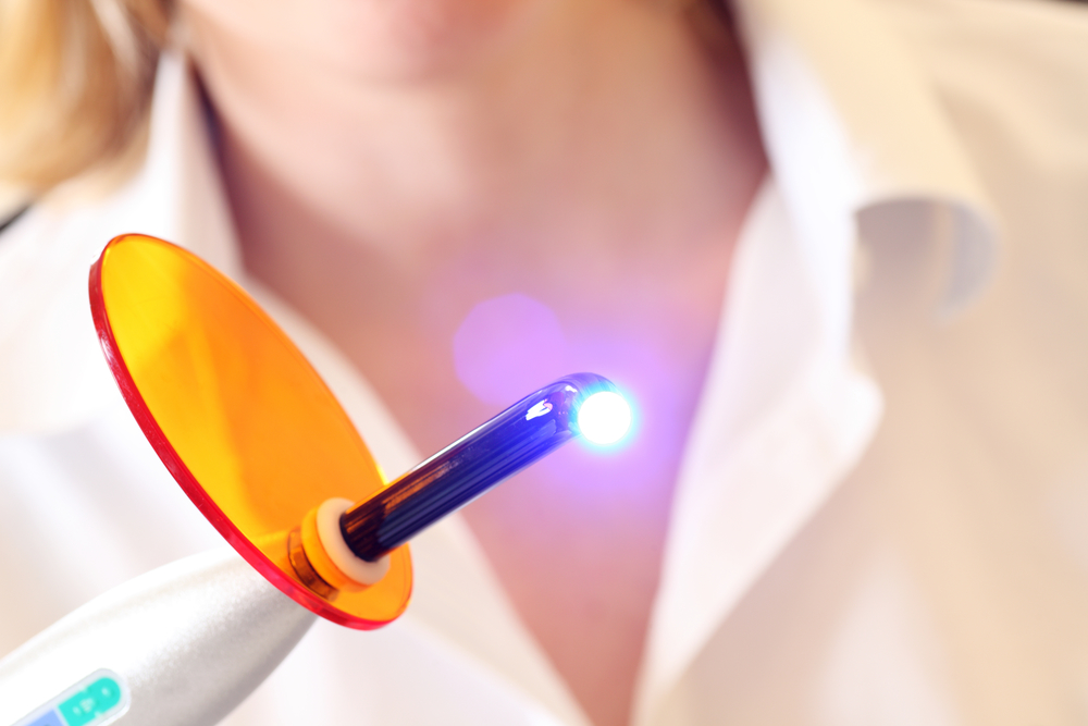 Dentist holds a lit dental curing UV light